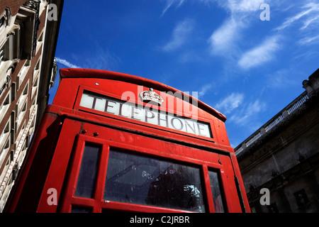 Low angle shot d'une cabine téléphonique rouge et bleu ciel à Londres, Angleterre, RU Banque D'Images