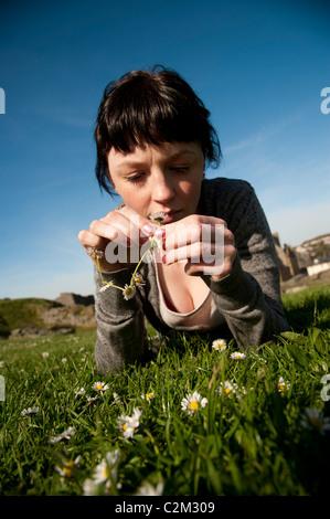 Une jeune femme faisant en marguerites UK Banque D'Images