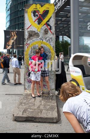 Les touristes posant devant une partie du mur de Berlin, Berlin, Allemagne Banque D'Images