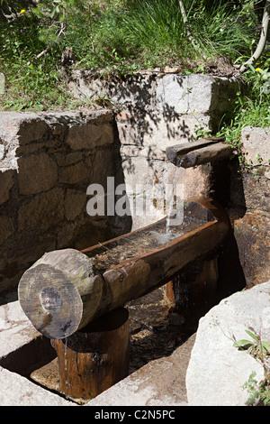 L'eau d'une source potable en bois et verser dans un trouch font de les Molleres Engolasters Andorra Banque D'Images