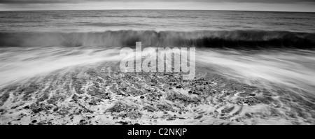 Vagues se brisant sur une plage de galets en noir et blanc Banque D'Images