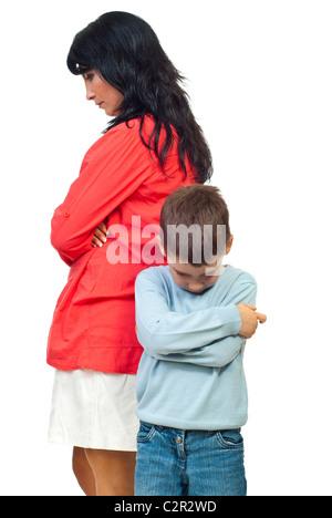 Triste mère et fils debout avec les mains croisées et regardant vers le bas après un conflit isolé sur fond blanc Banque D'Images