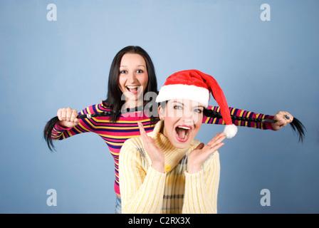 Un Funny Girl with Santa hat d'avoir ses tresses tiré par son amie et les deux rient et de crier et de s'amuser Banque D'Images