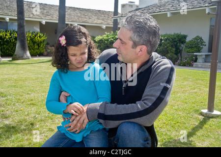 Un enfant de cinq ans Egyptian-American fille grimace de douleur d'un estomac à l'extérieur dans Laguna Niguel, CA.