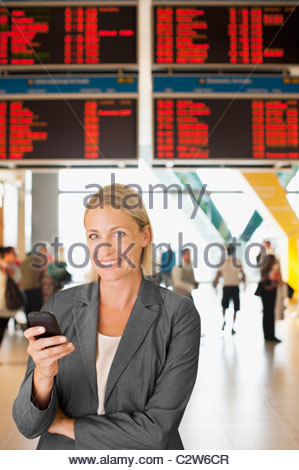 Businesswoman text messaging on cell phone in airport Banque D'Images
