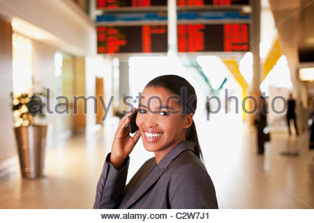 Businesswoman talking on cell phone in airport Banque D'Images