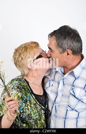 Portrait of mature couple 50s'embrasser devant image,woman holding Flowers Banque D'Images