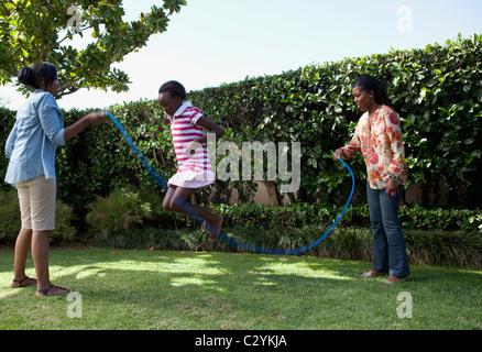 Corde à sauter enfants jouant dans le jardin, Johannesburg, Afrique du Sud Banque D'Images