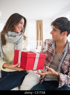 Woman handing mari cadeau de Noël Banque D'Images