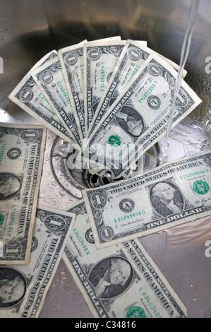 US dollars dans un évier avec de l'eau tournant concept bon argent. Banque D'Images