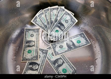 US dollars dans un évier. De l'argent en bas du drain concept. Banque D'Images