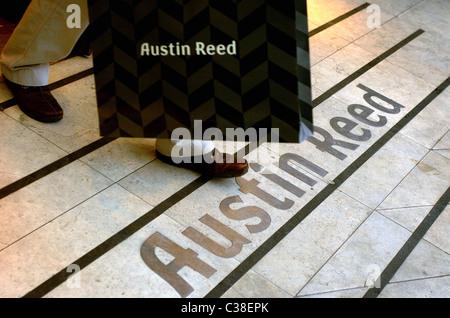 Un homme laissant une Austin Reed magasin avec ses achats.