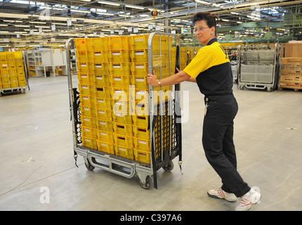 Un employé avec un chariot dans un centre de tri postal, Berlin, Allemagne Banque D'Images