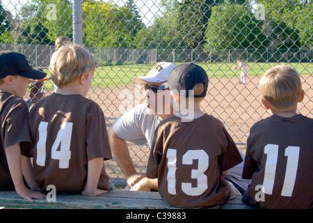 Instruire les jeunes francophones l'entraîneur sur le banc des joueurs de baseball. St Paul Minnesota MN USA Banque D'Images