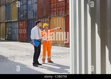 Mid adult businessman et d'ouvrier Debout près des conteneurs de fret. De forme horizontale, pleine longueur, copy space Banque D'Images