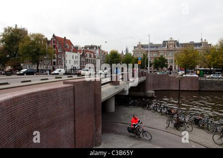 Un cycliste sous un pont près d'un canal à Amsterdam Banque D'Images