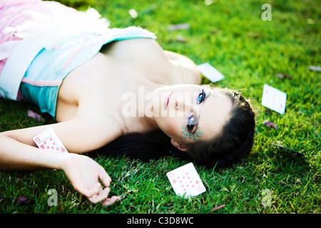 Jeune femme mystérieuse avec les cartes dans l'herbe autour de