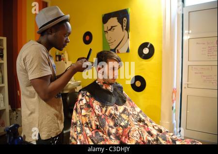 Young male hairdresser cutting cheveux du client dans le hip coiffure Banque D'Images
