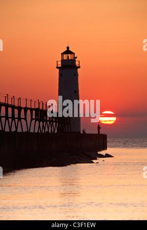 Un pêcheur solitaire est découpé à la base du phare sur une soirée d'été à la 5ème Avenue Beach de Manistee, Michigan Banque D'Images