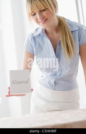 Serveuse mise réservés signe sur le tableau Banque D'Images