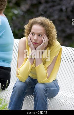 Les femmes en colère contre l'autre assis sur le banc de parc et de penser à l'expression de colère Banque D'Images