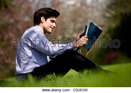 Un homme assis sur l'herbe, lisant le journal Banque D'Images