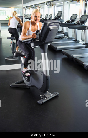 Woman exercising on bike in gym Banque D'Images
