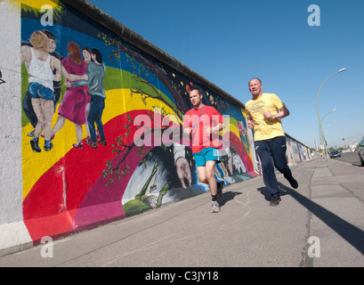 Les coureurs passent devant les murales peintes sur l'article original du mur de Berlin à l'East Side Gallery à Banque D'Images