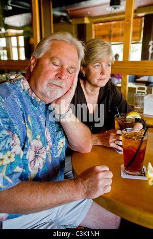 Un couple d'âge moyen semblait indifférent à l'ensemble plus de thés ensemble dans un Long Beach, CA, restaurant. MODEL