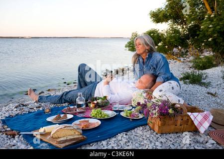 Mature couple having picnic on beach