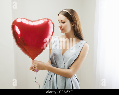 Woman holding heart shaped balloon Banque D'Images