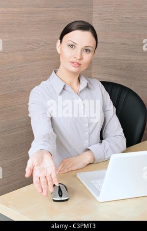 Portrait d'une belle jeune femme d'affaires sur l'ordinateur, de recevoir quelque chose. Arrière-plan de bureau. Banque D'Images