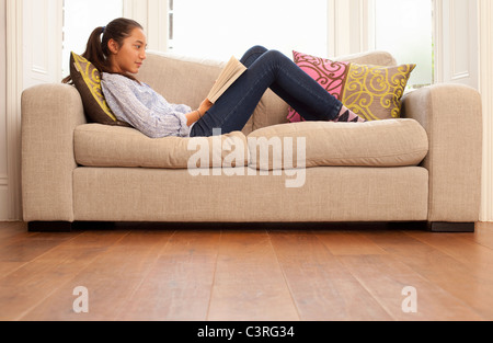 Teenage girl reading on sofa Banque D'Images