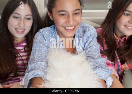 Les adolescentes en regardant la télé sur canapé Banque D'Images