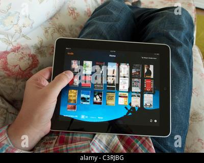 L'homme parcourt la bibliothèque numérique e-book sur Amazon Kindle app sur un écran tactile iPad tablet computer Banque D'Images