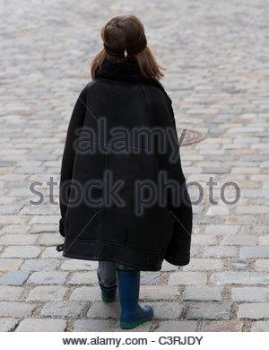 Bébé garçon enfant marche vue arrière portant la veste en peau de pères Banque D'Images