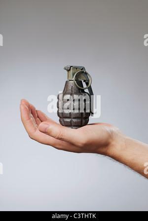 Homme tenant une grenade à main dans la main Banque D'Images