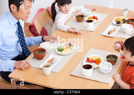 Père et deux enfants ayant le petit déjeuner Banque D'Images
