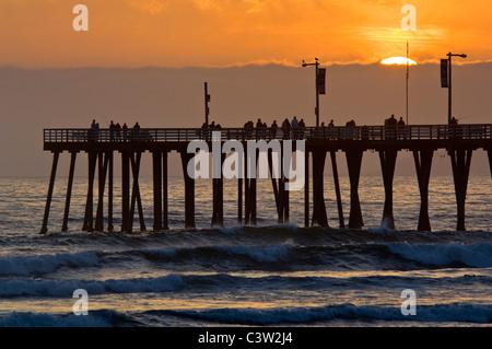 Coucher du soleil la lumière sur la jetée et les vagues de l'océan à Pismo Beach, San Luis Obispo County, Californie Banque D'Images