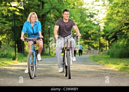 Heureux couple cycliste dans le parc de la ville Banque D'Images