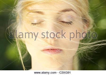 Close-up portrait of young woman with hair dans son visage Banque D'Images