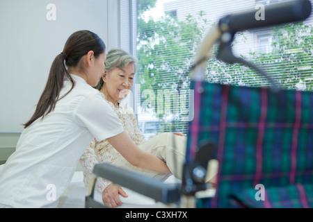 Levage infirmière senior woman pour fauteuil roulant du bed, Kanagawa Prefecture, Honshu, Japan Banque D'Images