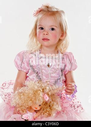 Jolie petite fille cute blonde vêtue de rose princess dress holding doll against white background looking at camera Banque D'Images