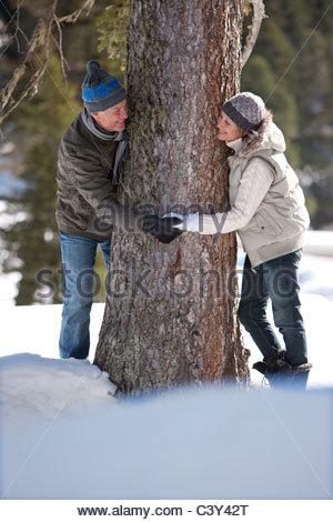 Couple holding hands autour d'arbre dans la neige Banque D'Images
