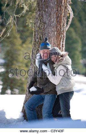 Couple hugging près de l'arbre à l'extérieur dans la neige Banque D'Images