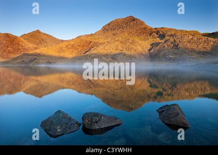 Tôt le matin, la lumière du soleil illumine Snowdon des rives d'un misty Llyn Llydaw, Parc National de Snowdonia, Banque D'Images