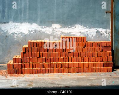 Briques alignés contre un mur dans un hutong chinois Banque D'Images