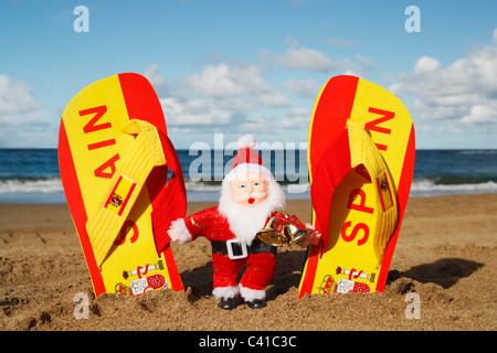 Le Père Noël et des tongs sur la plage en Espagne Banque D'Images