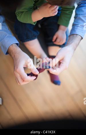 Père aider toddler mis sur les chaussettes, cropped Banque D'Images