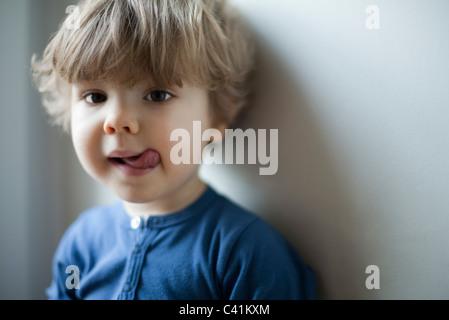 Petit garçon sticking out tongue, portrait Banque D'Images